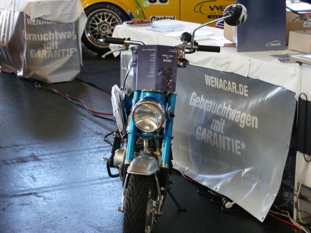 Eine blaue Honda Dax vor dem Stand der Wena - Car Produkt GmbH