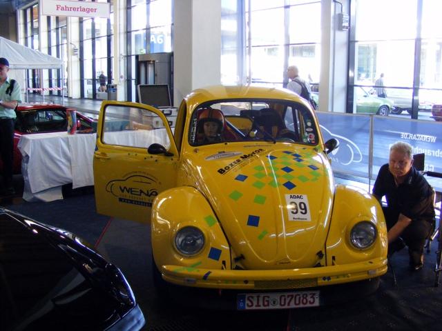 Ein gelber VW-Käfer Ralleywagen mit Wena-Aufdruck im Fahrerlager.