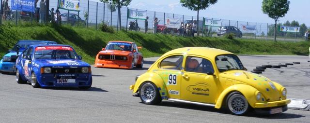 Vier klassische Sportwagen bei der Kurveneinfahrt